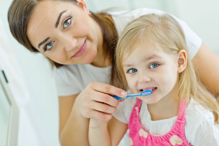 Mom and Daughter brushing their teeth - Pediatric Dentist in California, MD